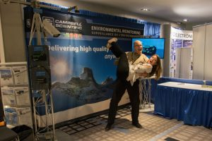 Photograph of two people at a Campbell Scientific exhibit stand at the CMOS congress. Man is shown holding woman in the air. Both are laughing.
