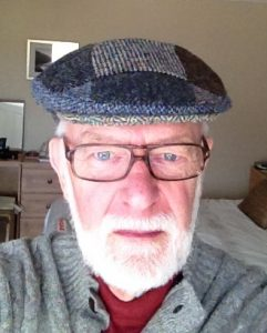 Photograph shows an older man with a white beard and glasses wearing a tweed hat.