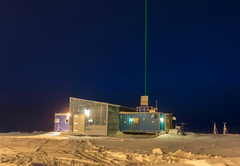 Photo shows a flat-roofed building with some instruments on the roof and a long antennae extending in to the air, at night. Exterior lights light up the snow in the foreground.