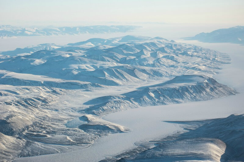 Photo shows an aerial long-distance view of a snow and ice landscape, mountains and a river channel, near the PEARL ridge lab at Eureka.