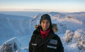 Photo shows a young caucasian man in his 20s, warmly dressed, with a long view of snow covered mountains in behind him.