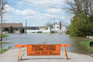 Photo shows a sign saying road closed with a flooded street in the background, Canada's top ten weather stories 2017 by David Phillips