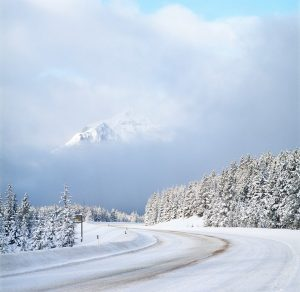 Photo shows a very snowy road, lined with trees, and snowcapped mountains in the distance, Canada's top ten weather stories 2017 by David Phillips