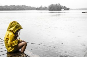 Photo shows a child in a yellow rain jacket with the hood up sitting at the side of a lake, Canada's top ten weather stories 2017 by David Phillips