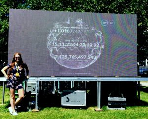 Samantha Mailhot is pictured standing beside a billboard sized projection of the climate clock, showing the time until we reach 1.5 degree of warming, on a sunny summer's day.