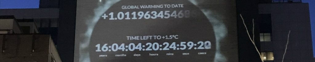 Photo shows a projection of the climate clock on the side of a building for the article by Samantha Mailhot for the CMOS Bulletin.