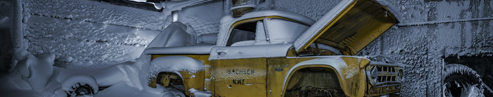 Image from Isachsen by aAron munson shows an old yellow pick up truck covered in snow, in a frozen garage