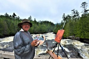 Phil Chadwick, en plein air EcoArtist and Meteorologist, pictured painting outside alongside a river surrounded by trees.