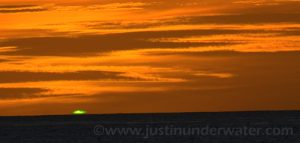 Photo of summer atmospheric phenomenon, Green Flash, article by Jim Young of CMOS. Photo shows a sunset and a small bright gleen glow at the horizon.