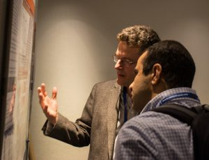 Photo shows two men looking at a scientific poster at the CMOS Congress