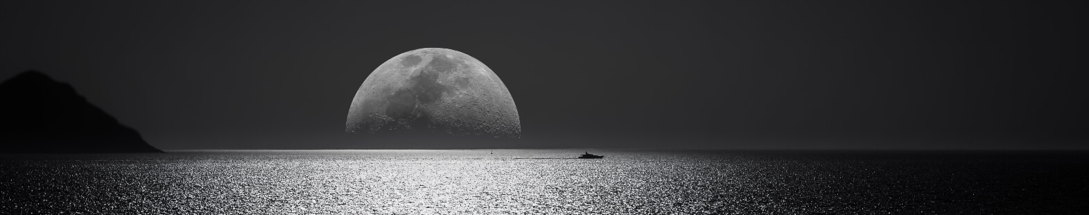 Banner image for The Lunar Atmosphere article by Paul Godin and all. Image shows a moon setting on the ocean, black and white image.