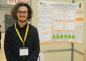 Photo shows a smiling Jean-Philippe Gilbert standing beside a scientific poster. He is in his early 20's, chin length dark hair, beard and moustache, with glasses.