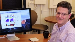 Photo shows a smiling Paul Kushner, caucasian male, clean shaven, 40's, dark hair and glasses, sitting adjacent to a computer screen.