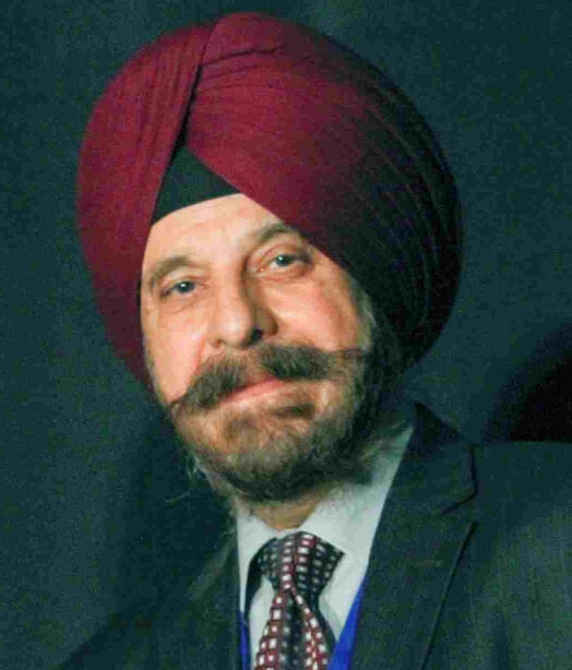 Photo shows a bearded Harinder Ahluwalia, president of IFMS, of middle eastern descent, smiling and wearing a burgundy turban.