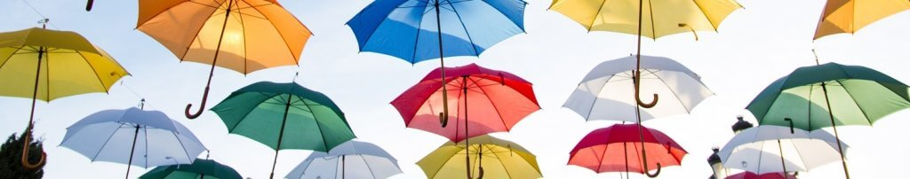 Photo showing colourful umbrellas floating in the sky. The banner image for the interview with IFMS president Harinder Ahluwalia