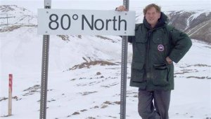 A photo of Jim Drummond, standing in an ARctic landscape at a sign that reads 80 degrees north