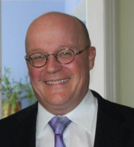 Photo of Michael Crowe, Author of ArcRCC article. A middle aged man, bald with glasses, smiling.