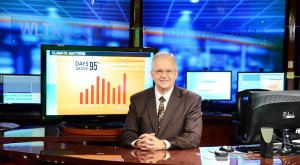 Photo shows a smiling weathercaster, Jim Gandy, sitting at a desk with several screens behind him, for the article by Bronwyn McIlroy-Young