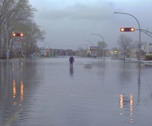 Photo of a man walking down a deserted flooded street in Montreal for the article by Bronwyn McIlroy-Young on weathercasters as climate change communicators