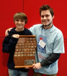 CMOS Awards photo shows a young boy standing with Gregory Steeves, holding an award.
