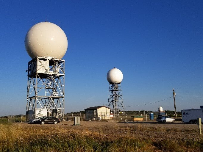 Photograph showing 2 radar towers against a blue sky
