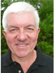 Photograph of a clean shaven man with white hair, smiling. Phil Chadwick