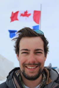 Photograph of a twenty-something smiling man, outside in the winter, with the Canadian flag behind him - Branden Walker
