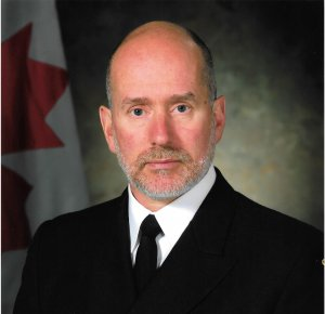 Headshot of a younger-middle aged Caucasian male with grey stubble beard, black suit and tie with Canadian flag in the background.