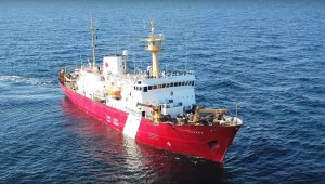 white and red research vessel facing you, on the ocean