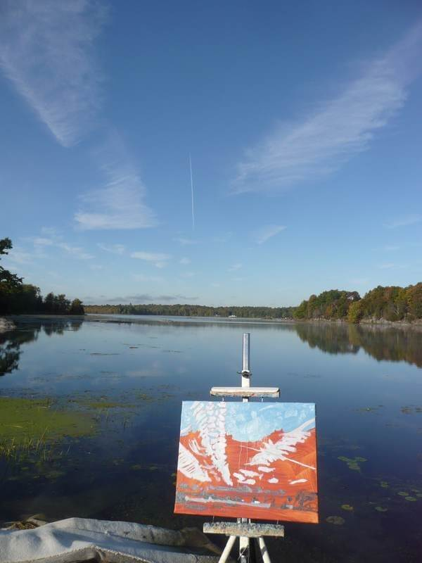landscape painting in progress on canvas on an easel by the lake. Painting is red, with white marks and blue sky..