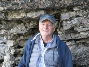 Older white male smiling wearing a blue basecall cap and blue layered clothing in front of a rock face