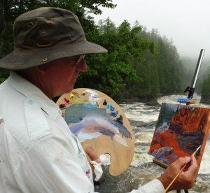 Caucasian man in white shirt and fishing cap painting on an easel by a river and forest
