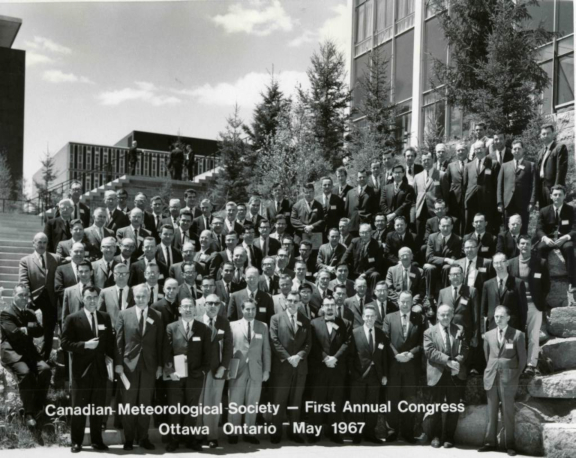 black and white photo of dozens of men in suits in front of a building at CMOS's first Congress in 1967.