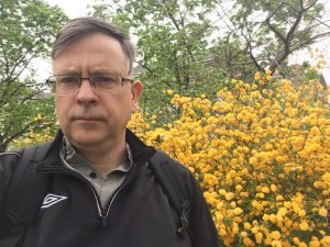 Caucasian man with glasses in front of yellow flowers