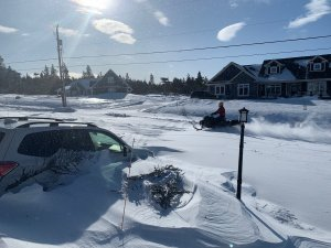 a photo taken of a snowstorm in St. John's Newfoundland featuring a car burried in snow and a person driving a snowmobile