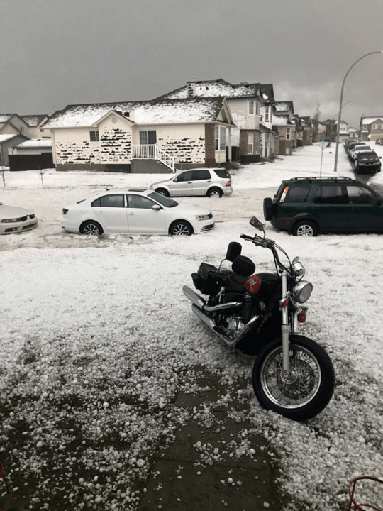 A photo of large hail on the ground taken from a driveway with a motorcycle on it