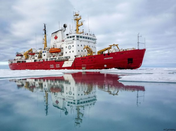 A red and white icebreaker with a perfect reflection on the water
