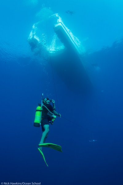 a scuba diver in the water under a boat