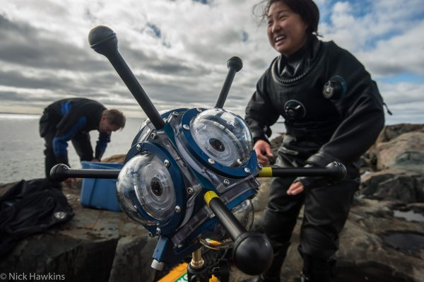 A person in a wetsuit who has just exited the water with a large scientific instrument for ocean monitoring in the foreground.