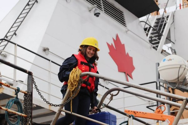 A person in an yellow helmet and orange life vest smiling and standing on a reserach vessel with a red maple leaf painted on the vessel