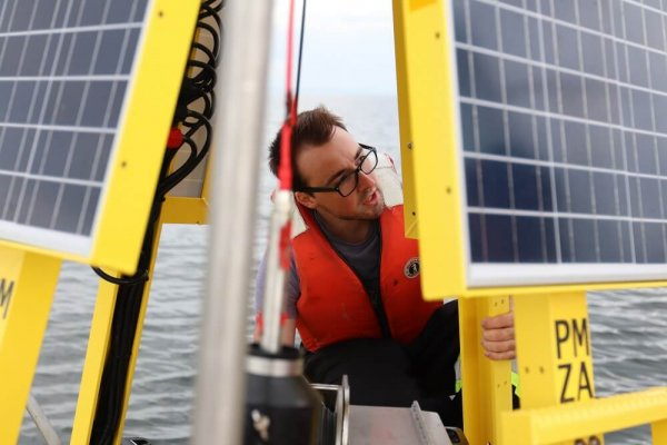 A person on a large buoy in the ocean with solar panels on it taking sampes
