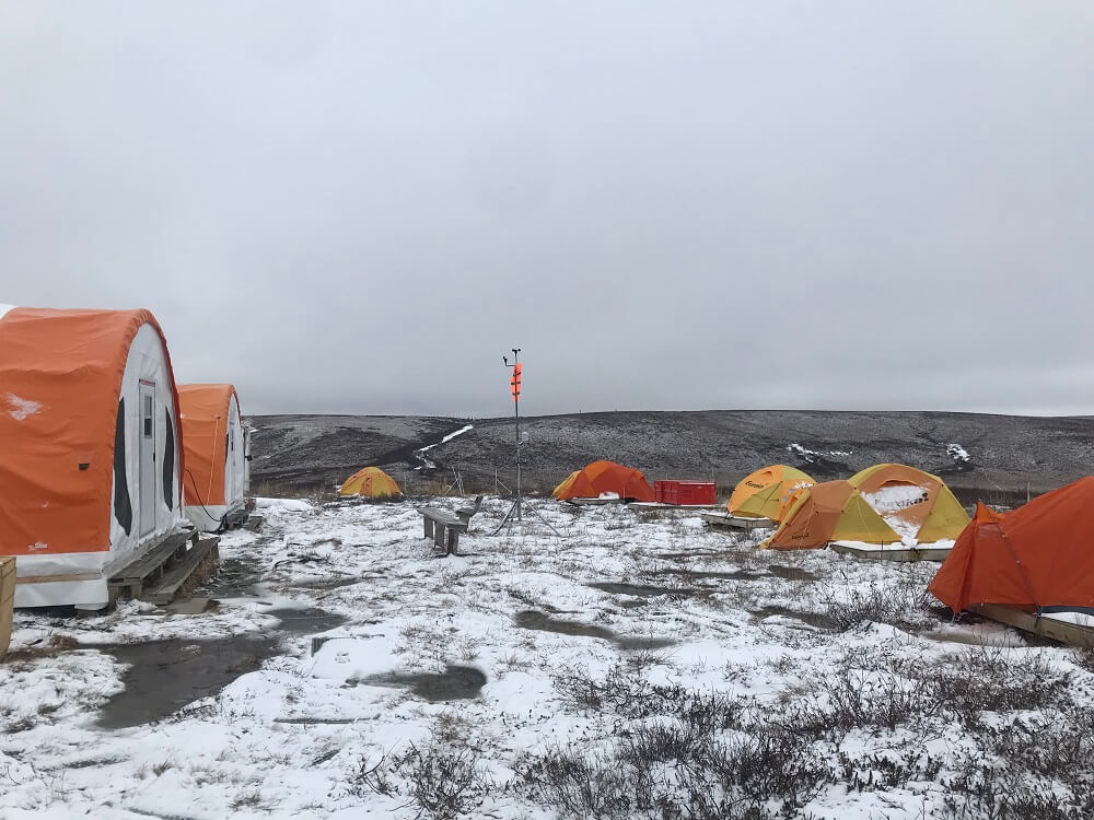 Several orange camping tents and two large prospector tents on the snowy tundra. Some scientific instruments set up between the tents.