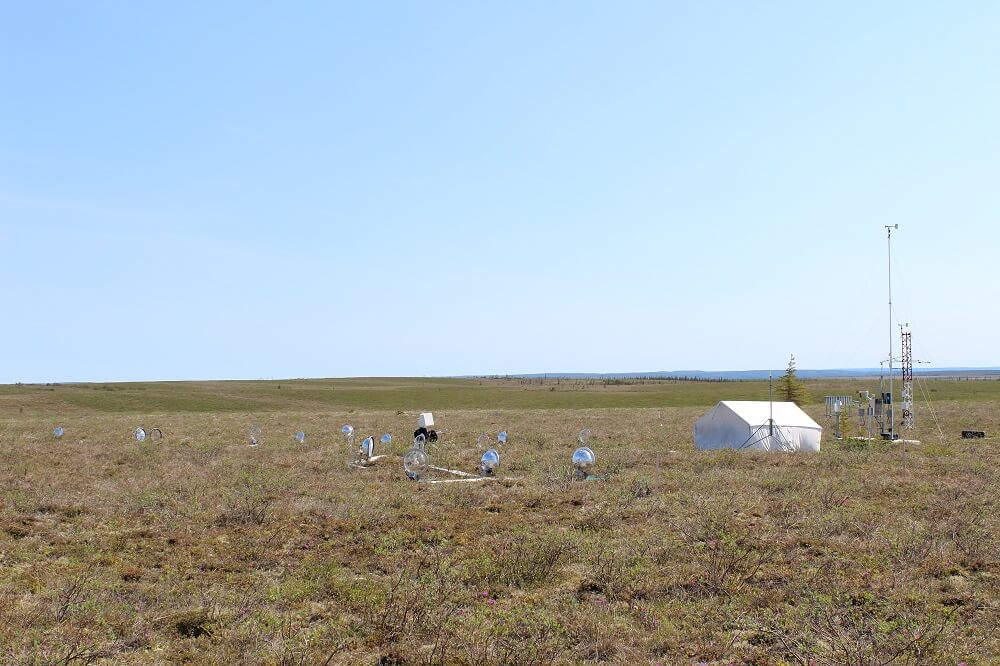 A landscape view of the tundra with a large white tent and scientific instruments on the landscape.