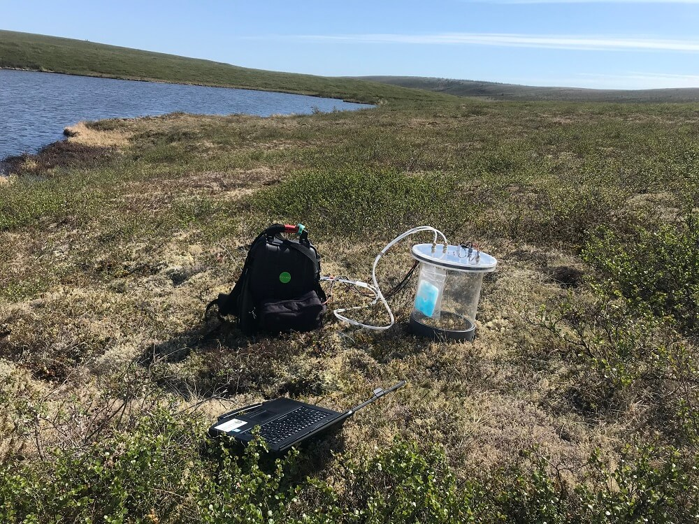 A backpack, a laptop and a transparent chamber sitting on the tundra next to a lake.
