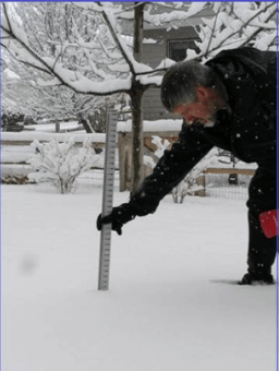 A man with grey hair wearing a black winter coat bending over in the snow with a ruler placed into the snow on the ground